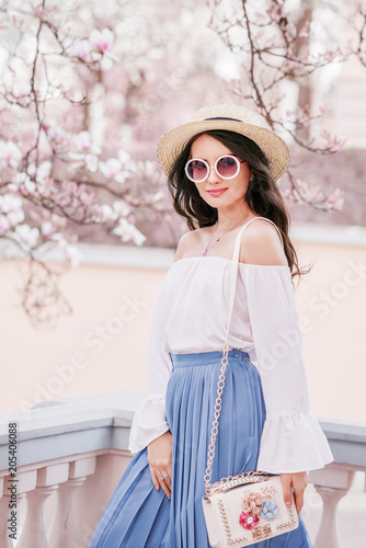 Vászonkép Outdoor portrait of young beautiful woman wearing stylish round  sunglasses, straw hat, cold shoulder blouse, pleated light blue skirt, with small white bag posing in street