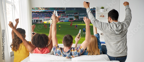 Fotobehang Stof leisure, sport and people concept - happy friends with bottles of non-alcoholic beer watching soccer or football on projector screen at home