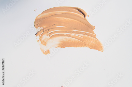 Poster texture of the liquid cream is beige, smears of the cream base on a white backgr