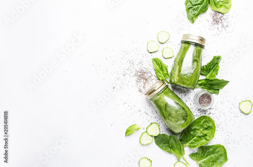 Green smoothies with spinach, cucumber and chia seeds, light background, top view