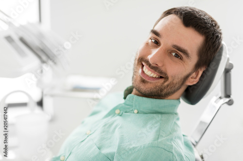 Stampa su Tela  medicine, dentistry and healthcare concept - happy smiling male patient on chair