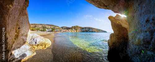 Fotomural  Matala beach with caves on the rocks that were used as a roman cemetery and at t