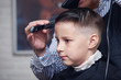 Barber is drying a hair to Caucasian boy in barbershop.