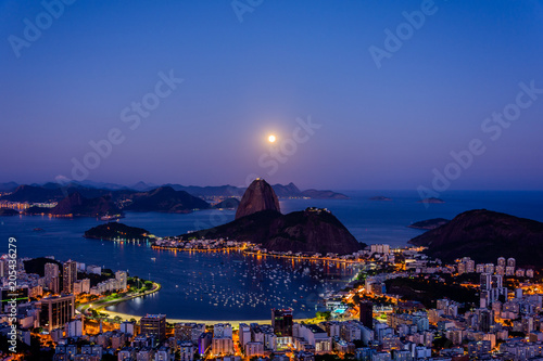 View to Pao de Acucar (Sugar Loaf Mountain) during beautiful full moon at Mirante Dona Marta (Dona Marta viewpoint) , Rio de Janeiro, Brazil