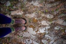 Two Feet Stading On A Muddy, Wet Path