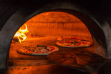 Original neapolitan pizza margherita in a traditional wood oven in Naples restaurant, Italy - 205447060