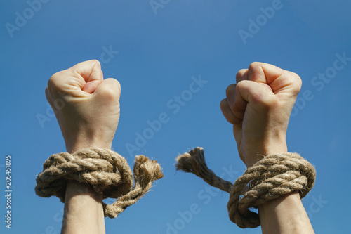 Fotografia  Hands free from shackles are stretched to the blue sky