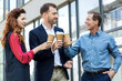 cheerful successful business team clinking with disposable cups of coffee