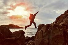 Jumping Man Hiker Over A Gap Between Two Rocks