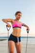 female athlete in earphones with smartphone in armband case doing exercise with stretching band on beach