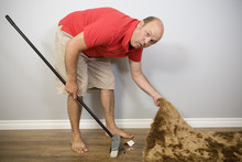 A Man Sweeping Things Under The Carpet.