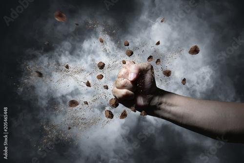 Valokuva  Unknown hand smashing stone with dark background .