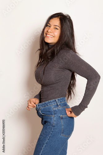 Latin woman in baggy pants, indoors, over a white wall Canvas Print