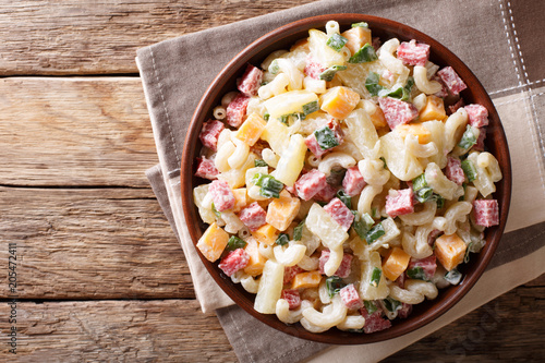 Hawaiian food: salad with pasta, ham, pineapple, onion, cheddar cheese with mayonnaise close-up in a bowl. horizontal top view