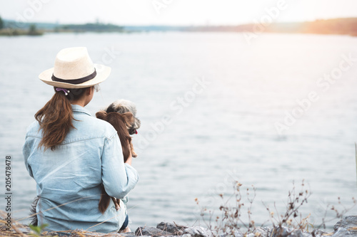 Happy young asian woman sitting with her dog beside reservoir. Tablou Canvas