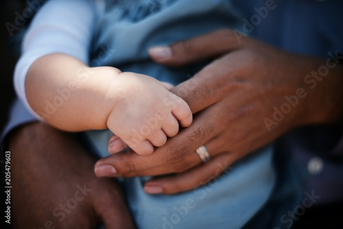 Hands of father and baby with different skin colors