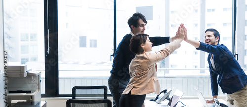 Photographie  Team work concept. Three people giving high five.