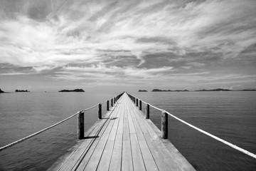 Fototapeta Mosty Black and white Landscape of wooden bridge in blue sea on tropical beach.