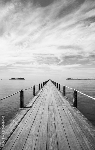 Black and white Landscape of wooden bridge in blue sea on tropical beach .