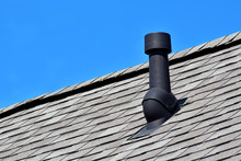 Black Air Ventilation Chimney On Grey Shingles Roof Of Residental House On Blue Sky Background With Copy Space For Text.
