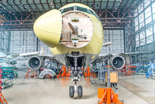 Passenger Airplane On Maintenance Of Engine And Fuselage Check Repair In Airport Hangar. With An Open Hood On The Nose Under The Cockpit Of Pilots.