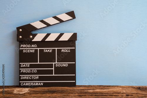 Cinema clapperboard on old wooden with blue wooden wall background - Movie entertainment concept