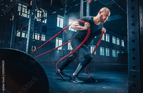 Deurstickers Fitness Men with battle rope battle ropes exercise in the fitness gym. CrossFit.