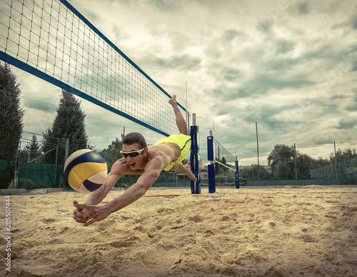 Beach Volleyball player in sunglasses flying for ball under sunl