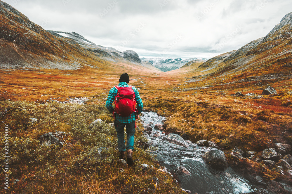 Fototapety, obrazy: Traveling Man tourist with backpack hiking in mountains landscape active healthy lifestyle adventure vacations in Scandinavia