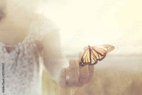 Foto op Canvas Bar a butterfly leans on a hand of a girl in the middle of nature