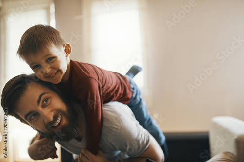 Portrait of happy father and little son playing together at home