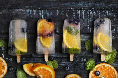 Homemade detox popsicles with blueberries, orange slices and mint leaves on black wood