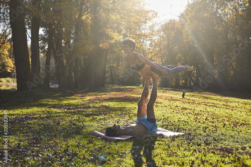 Couple yoga on forest glade, sun light