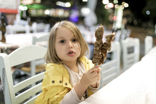Greece, portrait of little girl sitting in a restaurant with two Souvlaki meat skewers