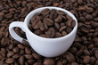 White cup full of coffee beans on the background of coffee beans. Close up