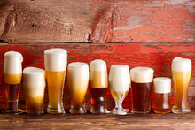 Multiple Frothy Beer Pints On Rustic Wooden Bench