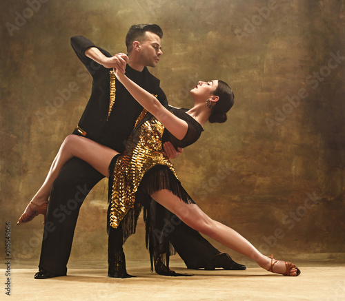 Fotografie, Obraz  Dance ballroom couple in gold dress dancing on studio background.