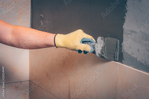Photo  The working tiler applies glue on the wall with a spatula before gluing, the tec