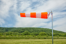 Red And White Wind Sock On Blue Sky, Mounting And Clouds Background