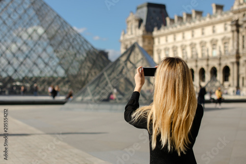 Fototapeta  Girl standing near Louvre and glass pyramind in black dress in Paris, talking photo by smartphone