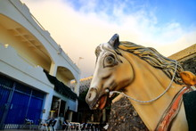 Closeup Of Yellow Toy Horse Head With Expressive Face. Evening, Yellowish Clouds. Room For Text. Selective Focus.
