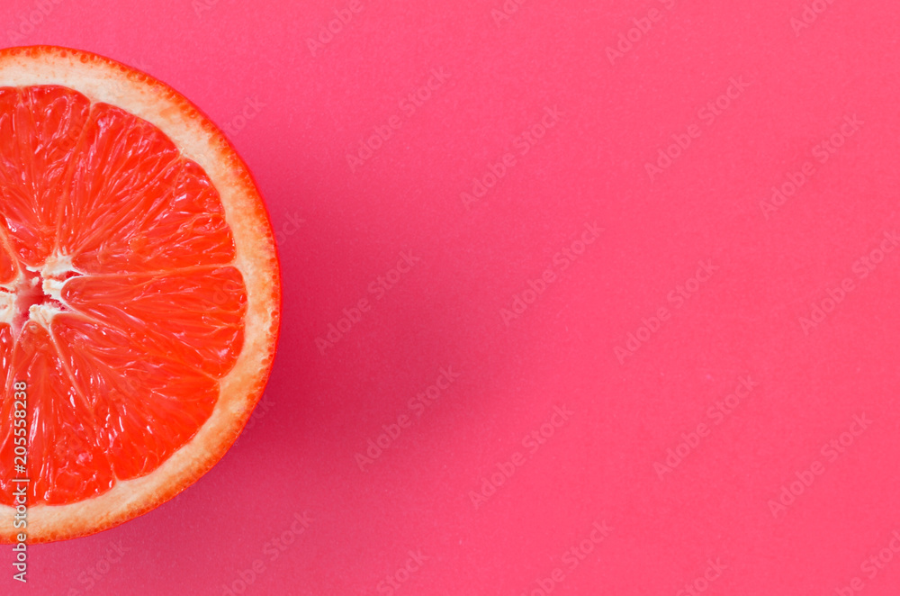 Fotografie, Obraz Top view of an one grapefruit slice on bright background in pink color