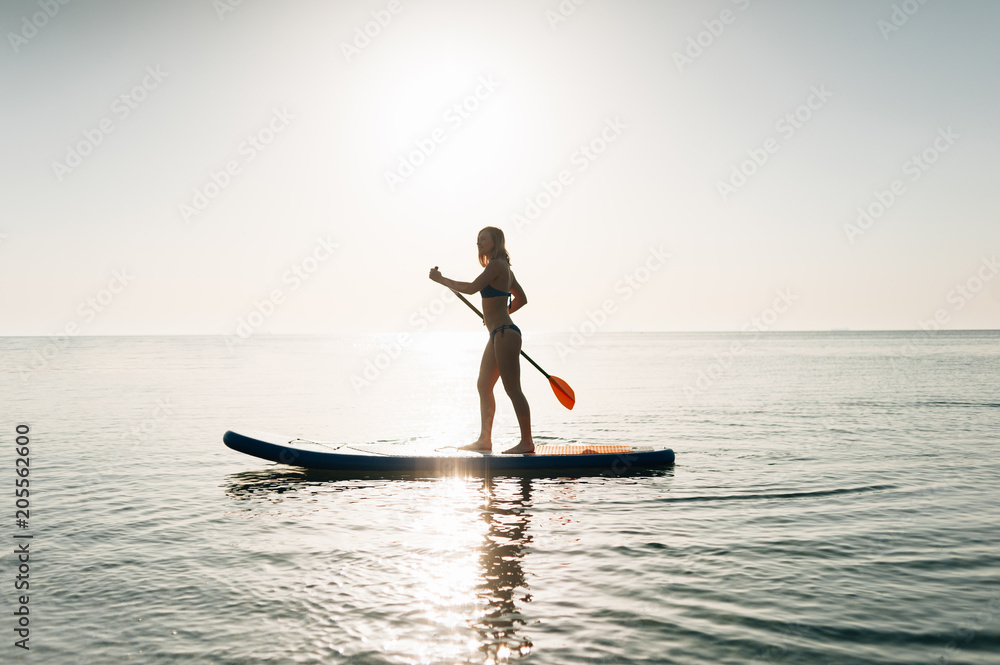 stand up paddle board woman paddleboarding on hawaii standing happy on paddleboard on blue water foto poster wandbilder bei europosters