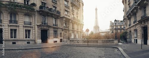 mała ulica Paryża z widokiem na słynną wieżę Eiffla w Paryżu w pochmurny deszczowy dzień z odrobiną słońca