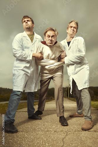 Stampa su Tela Two older retro paramedic freak hunters in medical coats catching crazy man in p