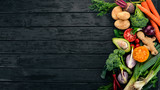 Healthy food. Vegetables and fruits. On a black wooden background. Top view. Copy space.