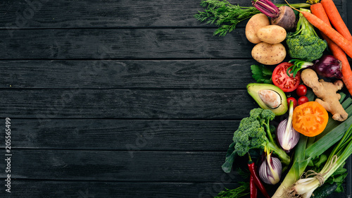 Poster de jardin Cuisine Healthy food. Vegetables and fruits. On a black wooden background. Top view. Copy space.
