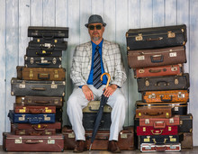 The Man Is Sitting On Old Suitcases
