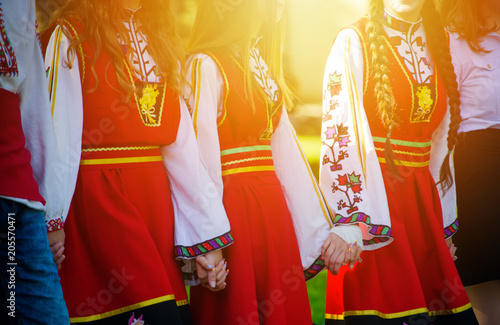Tuinposter Stierenvechten Girls in traditional Bulgarian costumes with red dresses and patterns on white shirts holding hands in the sunset. Concept of unity
