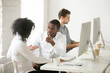Serious african colleagues discussing project together at workplace, black coworkers talking solving business problem in multiracial office, afro american teammates having disagreement or conflict at